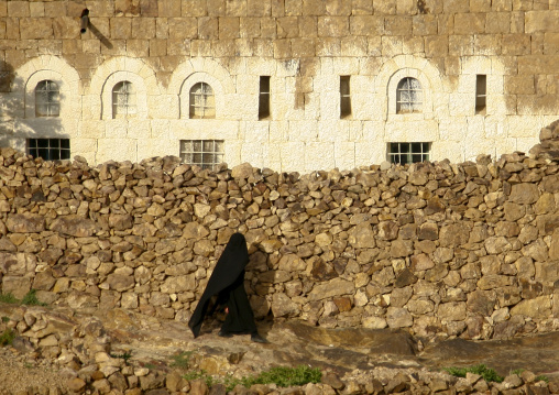 Veiled Woman In Black Passing By A Stone Wall, Shahara, Yemen