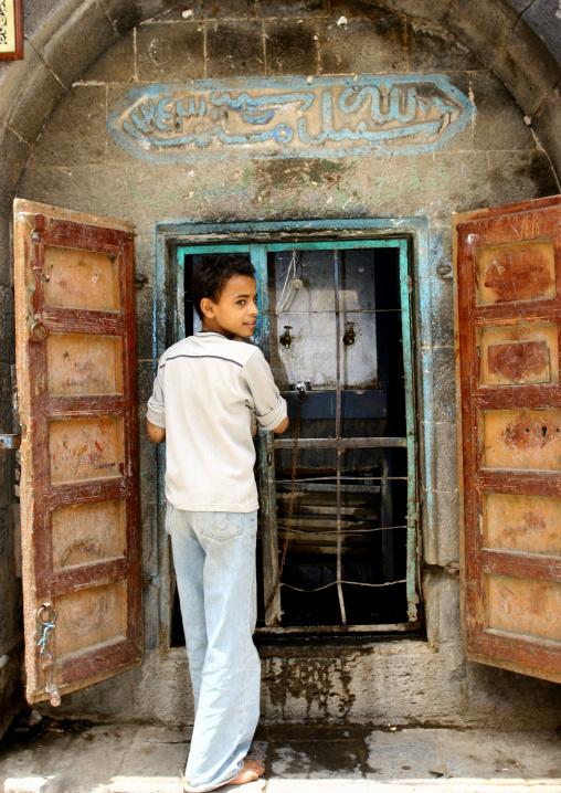 Arabic Boy In Tshirt And Jeans Drinking Water From A Street Fountain, Sanaa, Yemen