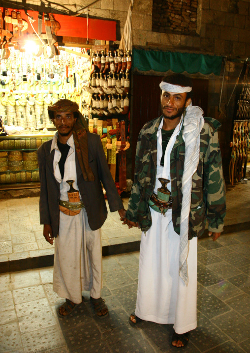 Two Men Wearing Jambiya Hold Hands In Front Of A Jambiya Shop, Sanaa, Yemen