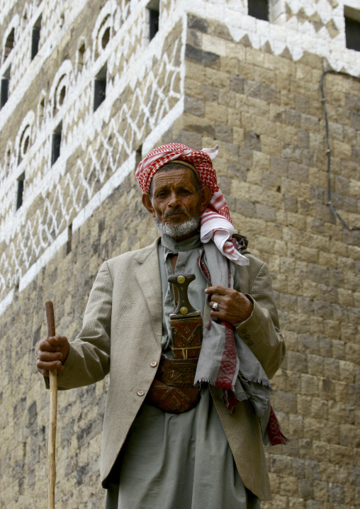 Old Man In Turban Posing Proudly In Front Of A Painted House In Al Hajjara, Yemen