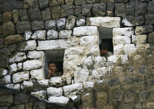 Two Kids Looking Outside From The Small Windows Of A House, Al Hajjara, Yemen
