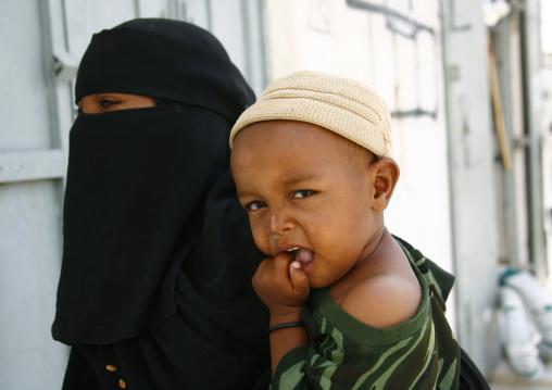 Yemeni Mother Wearing Niqab And Holding A Baby On Her Hip, Tarim, Yemen