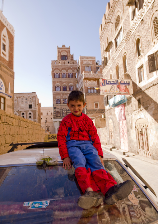 Smiling Kid Wearing A Spiderman Suit And Adult Shoes, Sitting On The Top Of A Car, Sanaa, Yemen