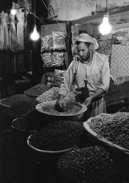 Yemeni Grocer Picking Up Grains In The Souq, Sanaa, Yemen