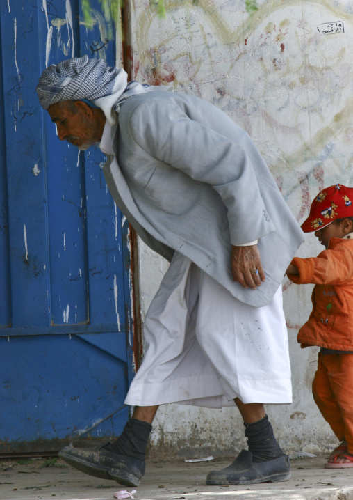 Old Bent Man Holding A Kid Hand In The Street, Yemen