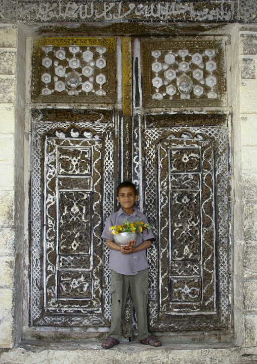 Smiling Boy Holding A Silver Ball Full Of Flowers In Front Of The Mosque Wooden Door In Ibb, Yemen