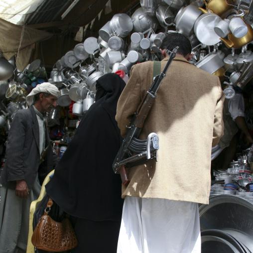 Man Carrying A Kalashnikov In Front Of A Crockery Shop, Sanaa Souq, Yemen
