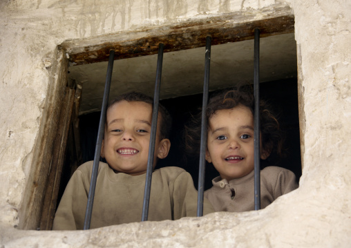 Children With Toothy Smiles Looking Down The Street Through A Window, Sanaa, Yemen
