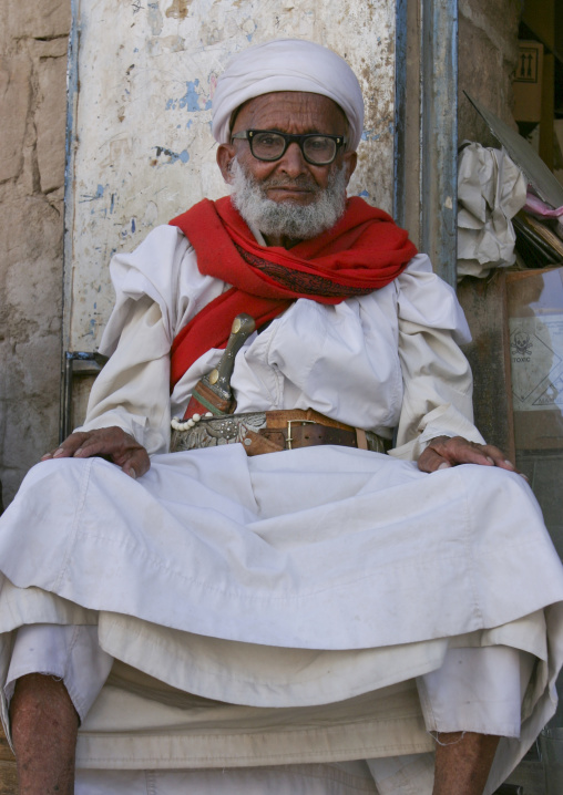 Proud Old Yemeni Man With Glasses And Dagger Sitting In Front Of A Shop, Rada,  Yemen