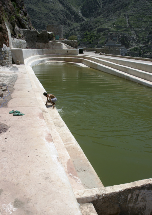 Man Taking A Bath In The  Water Cistern In The Mountain Village Of Hababa, Yemen