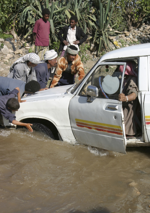 Group Of Men Trying To Help A Car Crossing A Wadi, Yemen