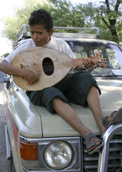 Boy Playing Oud On A Car, Thiama, Yemen