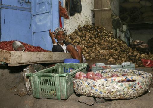 Seller Sitting On The Ground Among His Goods At Al Hodeidah Souq, Yemen
