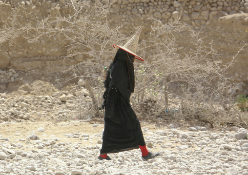 Hadramaut Woman Dressed In Black And Wearing A Cone Hat Passing By, Hadramaut, Yemen