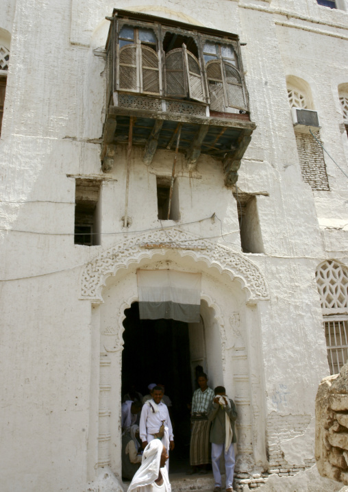 Men Standing At The Door Of A Builing Under A Mashrabiya And A Yemeni Flag With Faded Colours, Zabid, Yemen