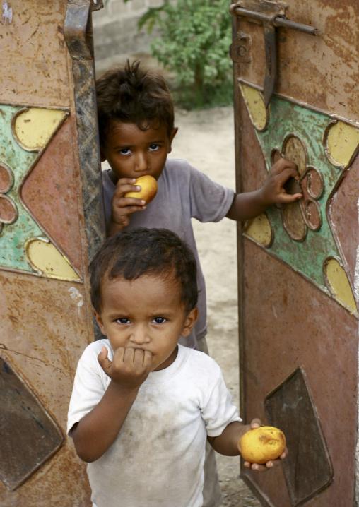 Two Young Boys Eating Fruits At A Door, Zabid, Yemen