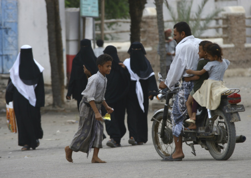 Street Scene, With Fully Veiled Women Walking And A Father Driving His Two Kids On A Motorbike, Zabid, Yemen
