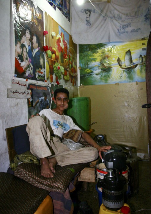 Young Man Lying Down And Chewing Qat In A Room Full Of Posters, Sanaa, Yemen