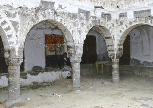 Man Sitting Under The Arcades Of Sanaa's Caravanserai, Yemen